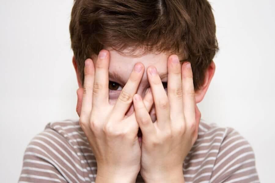 Blyghet under barndomen: blygt barn håller händerna för ansiktet