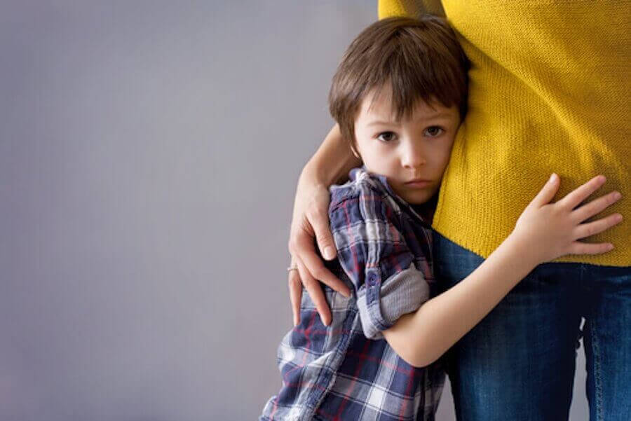 Blyghet under barndomen: blygt barn håller om sin mamma