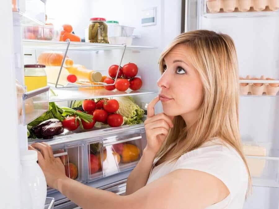 tankfull kvinna framför öppet kylskåp