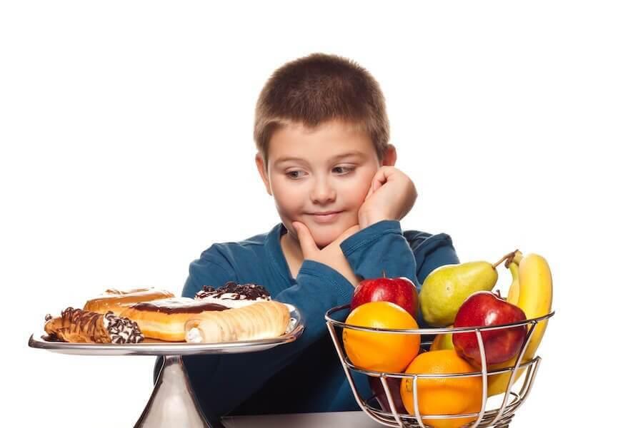 övervikt i barndomen: pojke tittar på bakverk bredvid en skål med frukt