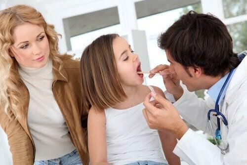 läkare kontrollerar tonsillerna på barn