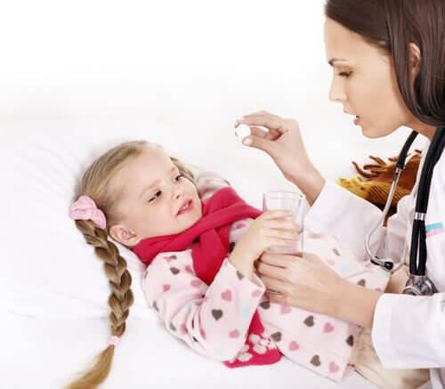 mamma ger medicin till barn i säng