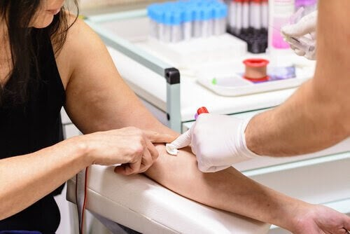 sjuksköterska tar blodprov på arm