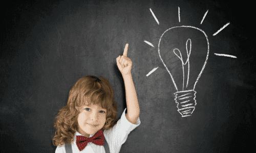 att lära sig språk i barndomen: pojke framför svart tavla med glödlampa ritad på