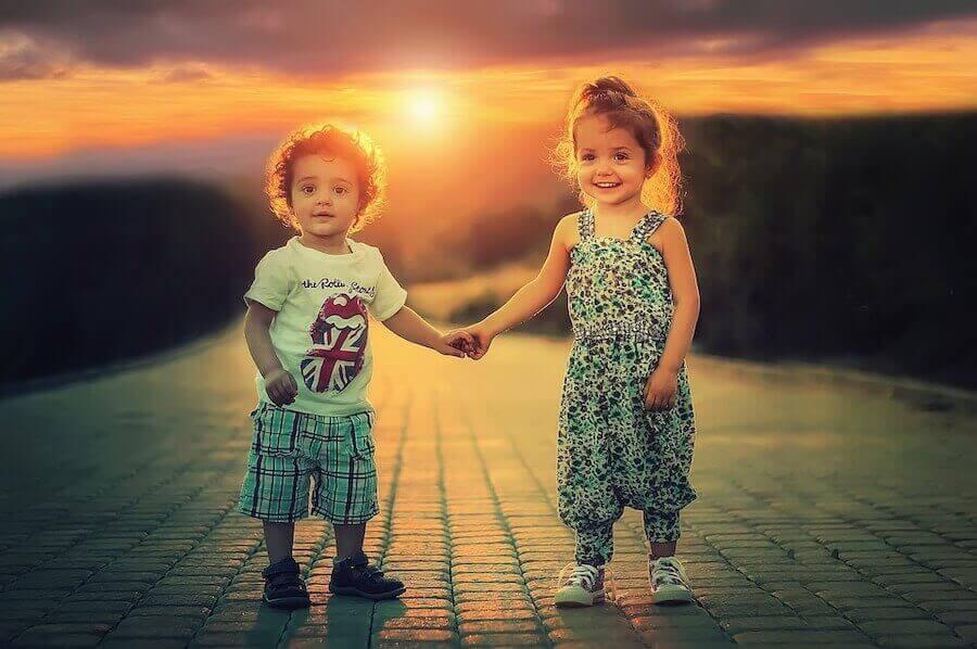 liten pojke och flicka håller handen i solnedgång