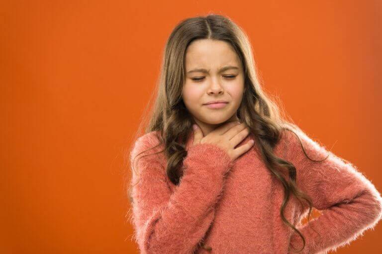knutor på stämbanden: flicka känner sig på halsen