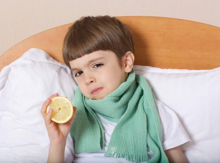 pojke med halsduk i säng håller upp en citron