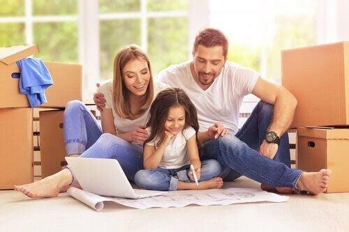 mamma, pappa och barn sitter på golvet och tittar på ritningar