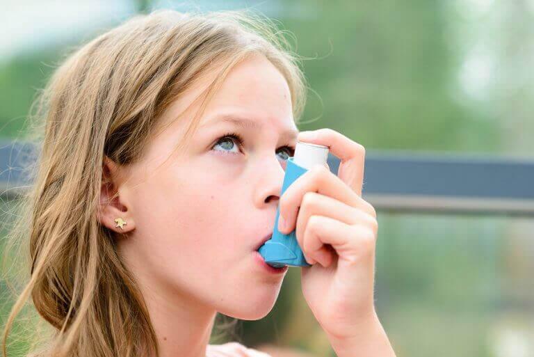 Flicka med astma använder inhalator