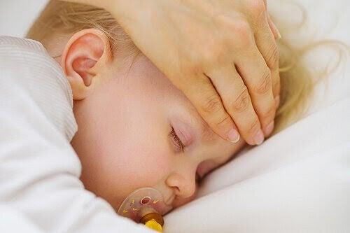 Hand känner på pannan på ett sovande barn