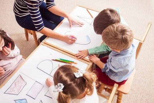 barn i skolmiljö ritar bokstäver