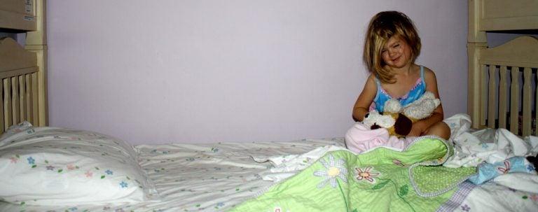 kissa i sängen: flicka vaken i sin säng