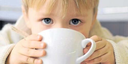Ett barn som dricker ur en kaffekopp.