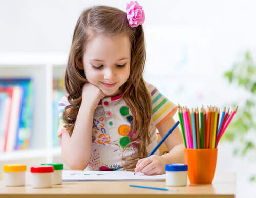 Flicka fokuserar på att måla en mandala.
