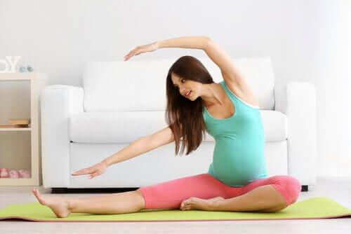 Gravid kvinna gör övningar för att stärka bäckenbotten.