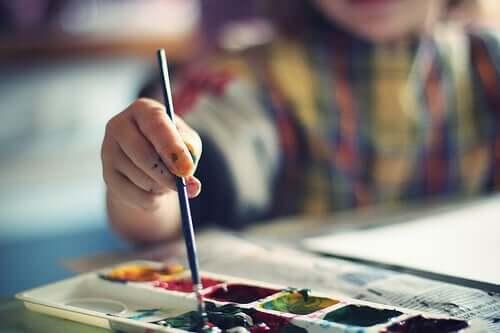 Barn målar mandala med vattenfärg.