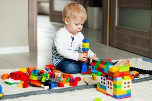 En pojke leker med lego.