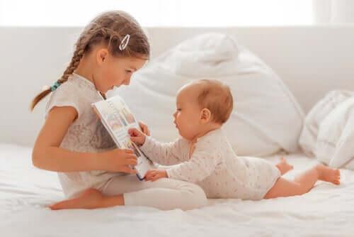 Systrar läser en bok ihop.
