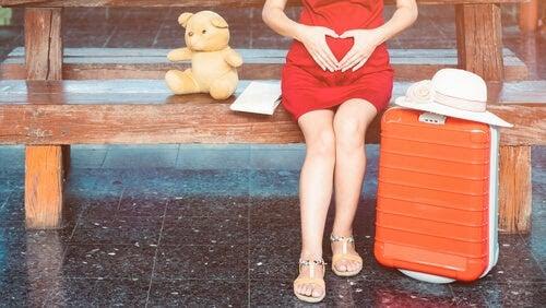gravid kvinna sitter på bänk med resväska och nalle