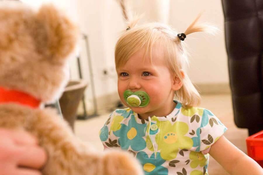 liten flicka med napp tittar på nalle