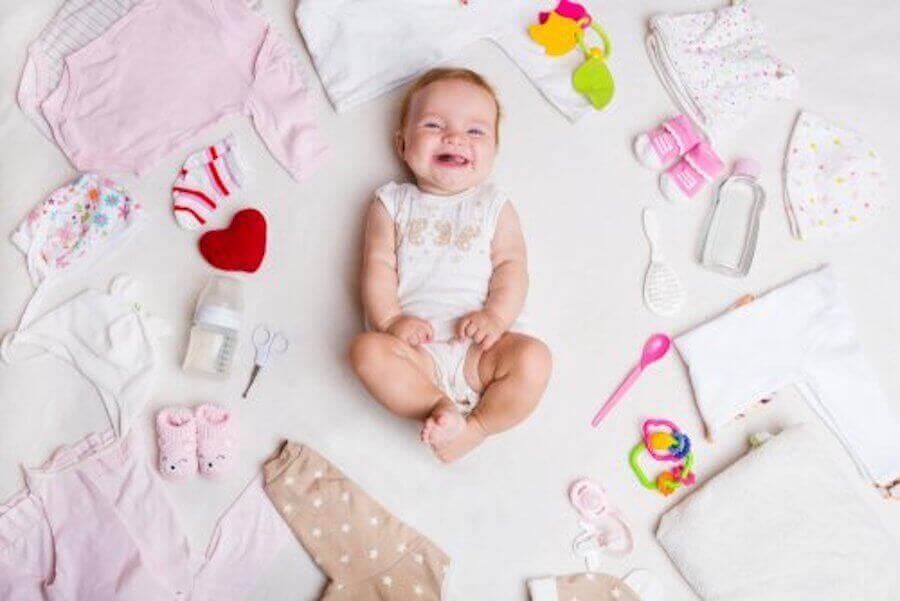 baby omgiven av babykläder och saker