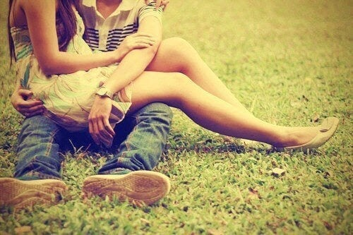 tonårsflicka sitter i knäet på tonårspojke