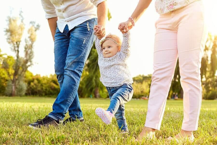 liten flicka håller föräldrar i händerna