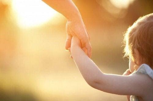 vuxen håller barns hand