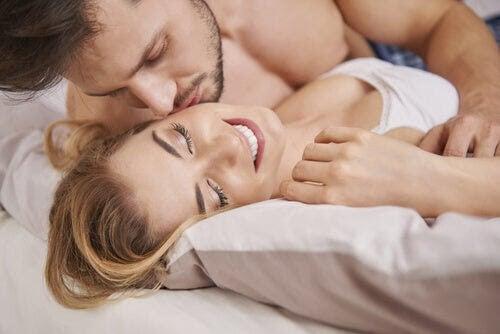 man kysser kvinna på säng