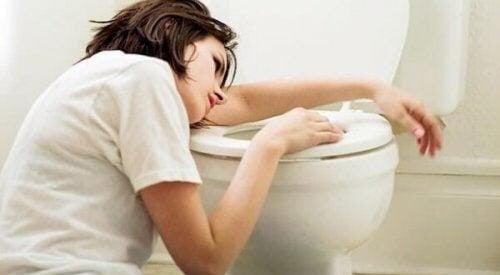 kvinna ser illamående ut vid toalettstol