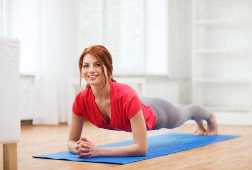 övningar som kan stärka din mage: glad kvinna gör plankan