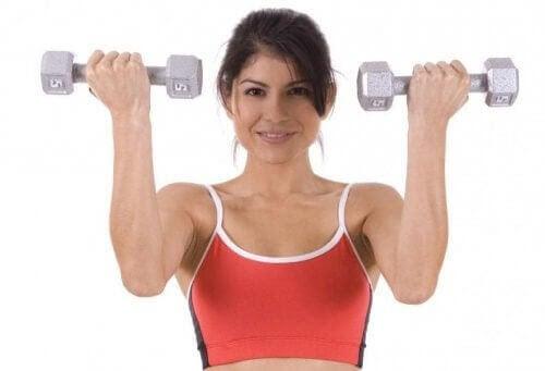 övningar som kan stärka din mage: glad kvinna håller upp hantlar
