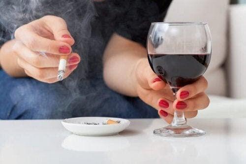 alkohol kan påverka din baby: gravid kvinna håller i ett glas vin och en cigarrett