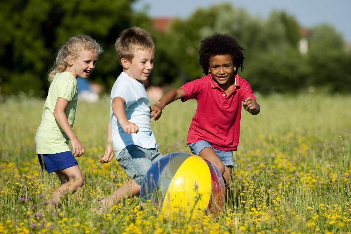 tre barn leker med boll