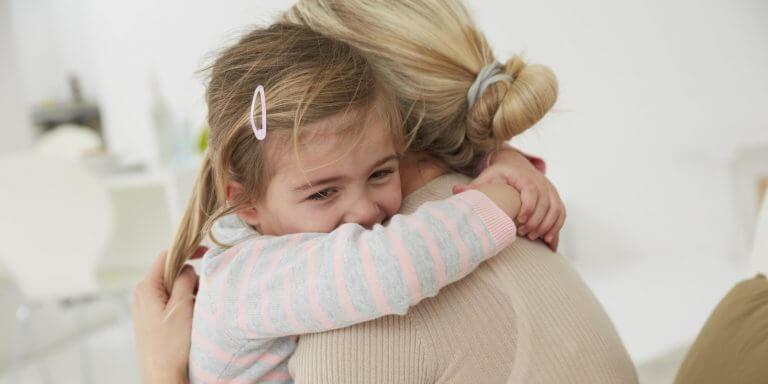 Flicka som kramar mamma.