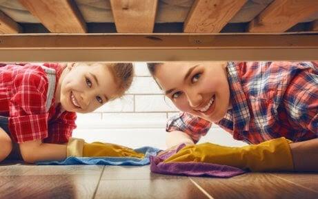 mamma och barn städar under sängen