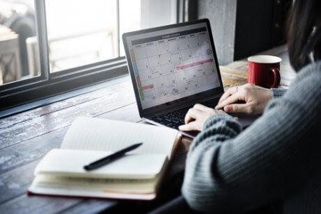 kvinna sitter vid laptop med kalender