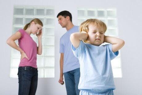 barn håller för öronen med föräldrar som bråkar i bakgrunden