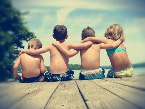 barn på brygga håller varandra om ryggen