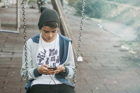 tonåring på gunga med mobil