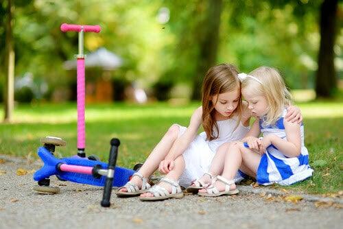 Interpersonell intelligens: större flicka hjälper liten flicka som trillat av sparkcykel