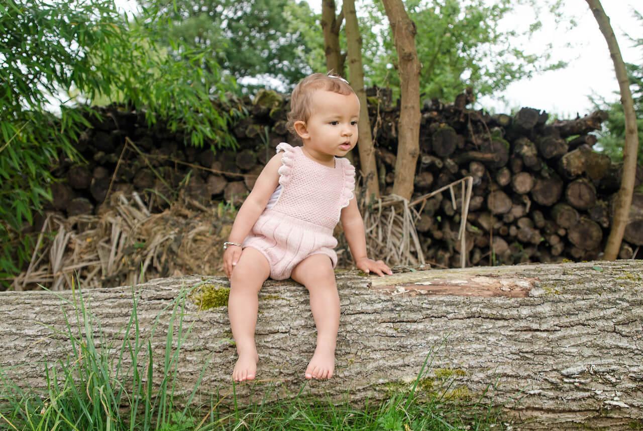 liten flicka sitter på trädstam