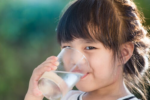 Urinvägsinfektioner hos barn: flicka dricker ett glas vatten