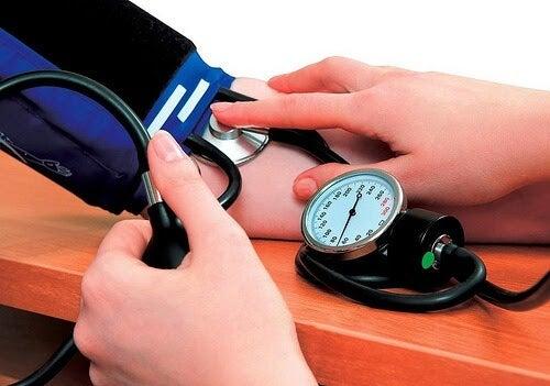 Högt blodtryck hos barn: läkare tar blodtrycket på barn