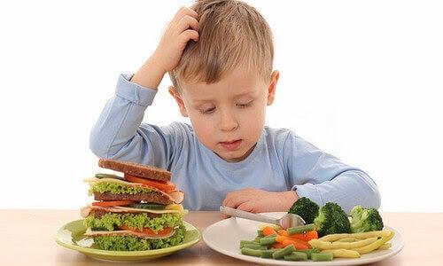 pojke tittar på mat och kliar sig i huvudet