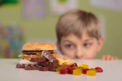 pojke tittar på hamburgare och godis