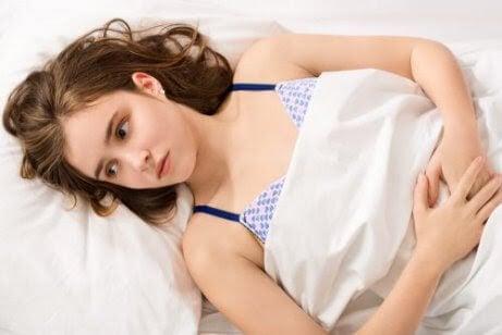 kvinna ser lidande ut i säng