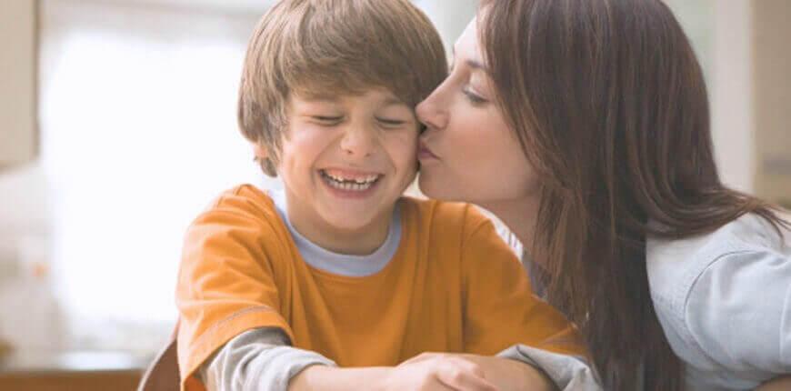 glad pojke får en puss av sin mamma
