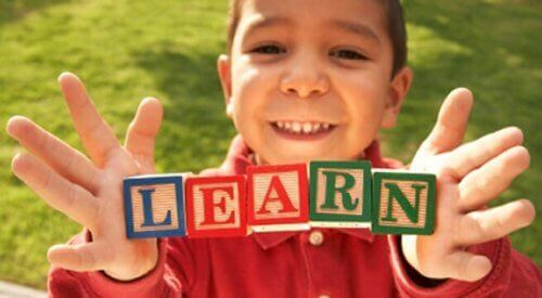 "Ett barn håller klossar som bildar ordet ""learn""."
