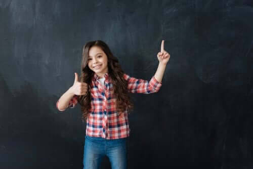Betydelsen av att bygga motståndskraft hos barn: flicka gör tummen upp framför svart tavla